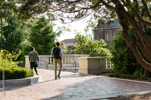 Leinwand Poster male and female students walking on campus in gold light with trees