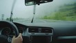 POV shot from inside hybrid car of woman behing steering wheel navigating through foggy dangerous mountain road at rainy day and drives in dark tunnels with lot of traffic.