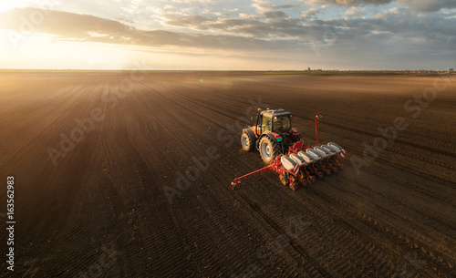 Foto  Farmer with tractor seeding