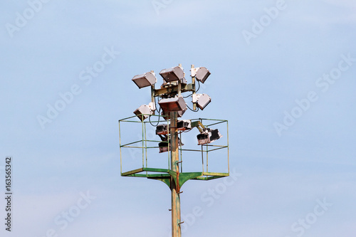 Stadium floodlight tower with reflectors with blue sky