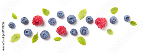Fresh blueberries with leaves and raspberries, berry ornament isolated on white background, top view