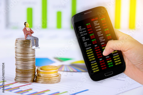 Hand holdind smartphone and stock charts screen with businessman is taking profit from trading babkground Poster