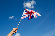 British Flag In Hand Against Blue Sky.