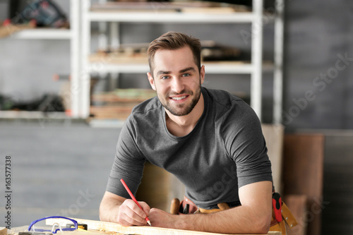 Young smiling carpenter working in light shop