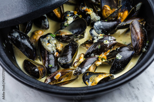 Valokuva  Soup of mussels creamy in black bowl on marbel surface.