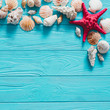 Summer sea background - shells, star on a wooden blue background.