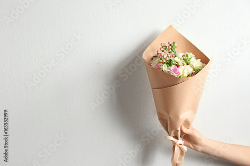 Fotografía  Woman holding beautiful bouquet with freesia on light background