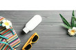 Summer vacation concept. Wooden board with beach accessories on light background