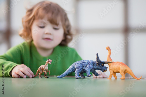 toddler kid playing with a toy dinosaur