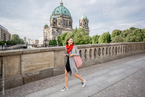 Spoed Fotobehang Berlijn Young woman tourist with photo camera enjoying traveling in Berlin city walking on the old bridge near the famous cathedral