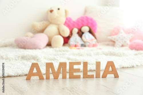 Photo Baby name AMELIA composed of wooden letters on floor