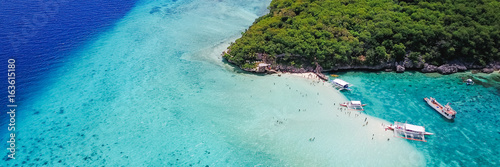 Valokuva  Aerial view of sandy beach with tourists swimming in beautiful clear sea water of the Sumilon island beach landing near Oslob, Cebu, Philippines