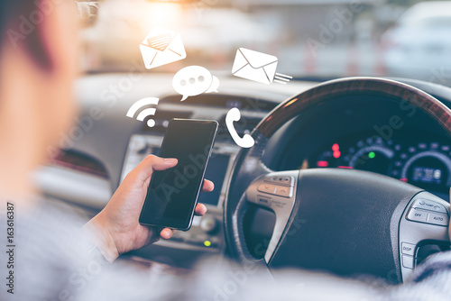 Obraz na plátně  Man using smartphone while driving the car