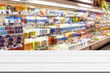 Abstract blur and defocused milk and yogurt department in supermarket or retail store interior for background and empty wooden table space platform for present product.