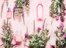 Natural Cosmetic Products Setting With Various Bottles And Fresh Herbs And Flowers On Pink Background, Top View, Flat Lay. Beauty, Skin, Hair Or Body Care Concept