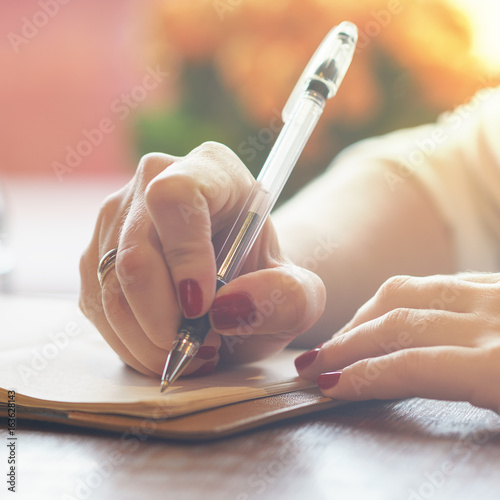 Stampa su Tela woman's hand with red nails writing some message note or letter to notebook by p