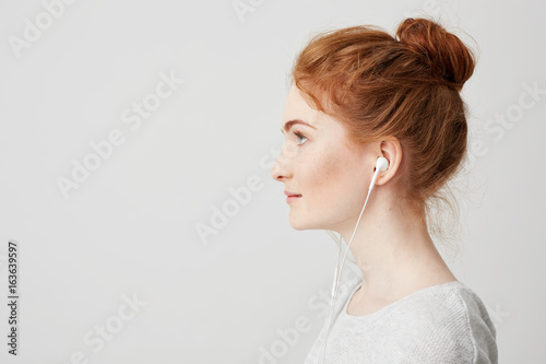 Recess Fitting Hair Salon Profile portrait of young beautiful tender redhead girl with bun in headphones smiling over white background.