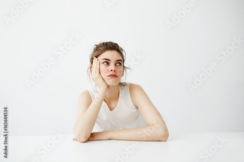 Fotografie, Obraz  Bored tired young pretty girl with bun thinking dreaming sitting at table over white background