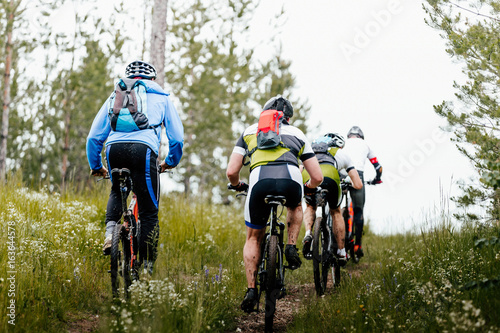Foto op Plexiglas Fietsen group of athletes mountain biking on forest trail