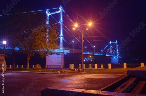 Fototapeta Pedestrian bridge over the Ural River / Photo taken in Russia, in the city of Orenburg, at night