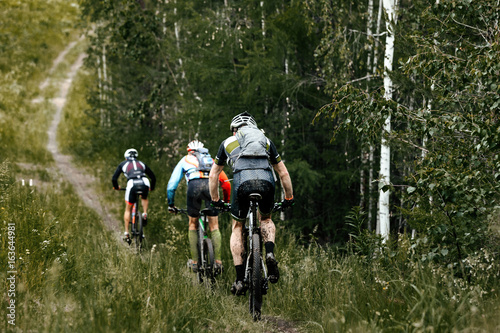 group athletes cyclist mountainbike riding forest trail