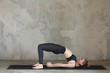 Young woman practicing Bridge, Setu Bandhasana yoga pose against texturized wall / urban background