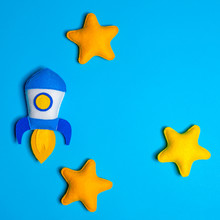 Rocket Takes Off. Hand Made Felt Toys. Space Ship With Yellow Stars On Lue Background.