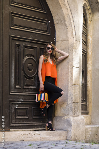 Elegant woman leaning at a wooden door Poster
