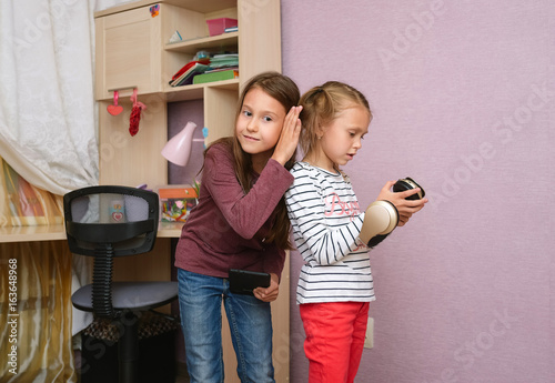 Teens Playing Tablet And Listening To Music With Headphones Naughty And Funny Fight