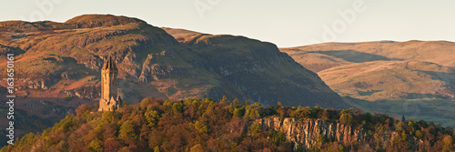 Fotografia The National Wallace Monument standing on the top of Abbey Craig rock with the Ochil Hills at the background