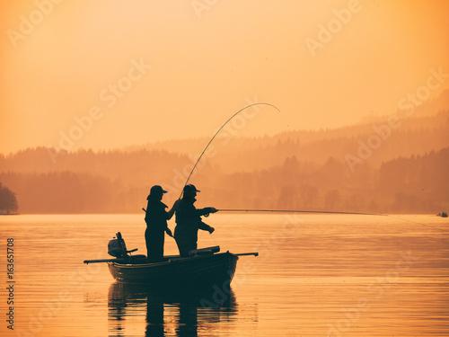 Fototapeta Silhouette of man fishing on lake from boat at sunset