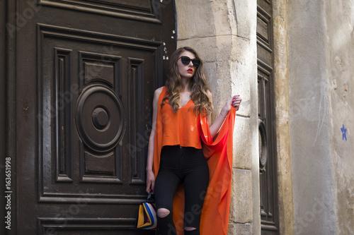 Elegant woman wearing orange shirt and black jeans Poster
