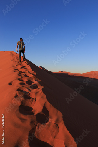 Fotografie, Obraz  Man  on sand dune in desert during sunrise