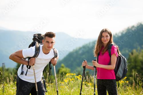 Fototapeta active Beautiful young couple hiking ina nature climbing hill or mountain - man and woman trekking obraz