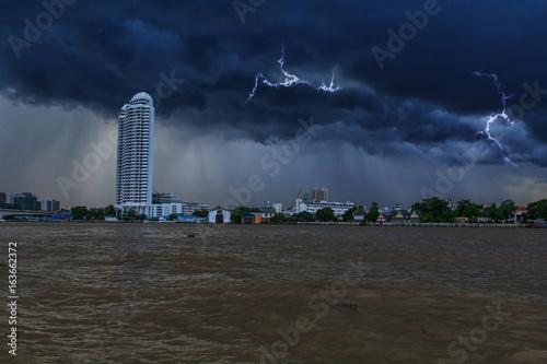 Plakat Ciemna obłoczna burza w mieście blisko rzeki / deszczu przybycia na niebie w miasto widoku