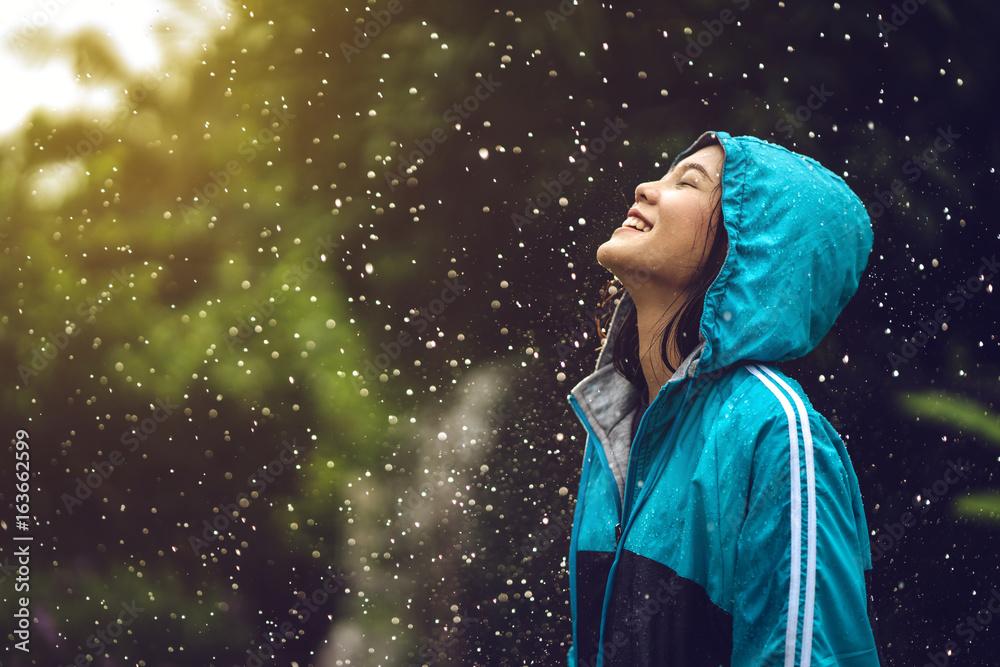 Fototapeta Asian woman wearing a raincoat outdoors. She is happy.
