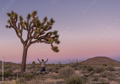 Poster Afrique Woman Leaps Under Large Joshua Tree
