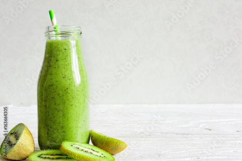 Foto op Plexiglas Milkshake bottle of green smoothie with fresh kiwi and banana fruits and berries
