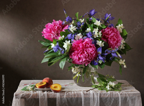 Bouquet of flowers in a vase and peaches.