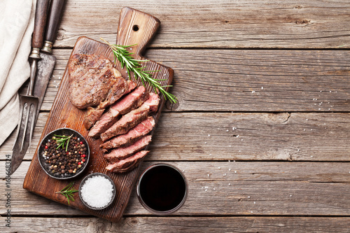 Foto op Plexiglas Grill / Barbecue Grilled beef steak with spices on cutting board