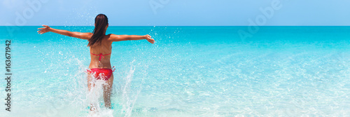 Fototapeta Summer fun beach woman splashing water with open arms banner. Panorama landscape of tropical ocean on travel holiday. Bikini girl running in freedom and joy with hands up enjoying the sun. obraz