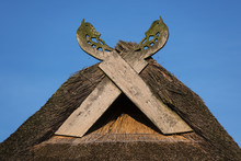 Wooden Gabled Boards In The Form Of Horse Heads On A Thatched Roof Against A Blue Sky, Typical Of Traditional Houses In Northern Germany