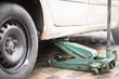 Replacing wheels on a car, one jack hold the body in the raised position