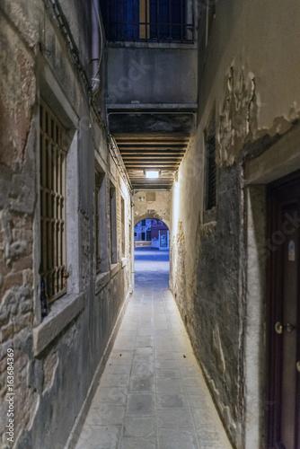 Tuinposter Oude verlaten gebouwen Very narrow cobblestone alley at night in Venice, Italy