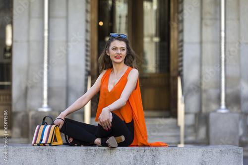 Smiling elegant woman in tailor seat Poster