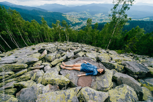 Young, lonely traveler girl lying at rocky stones high at mountains and meditating Poster