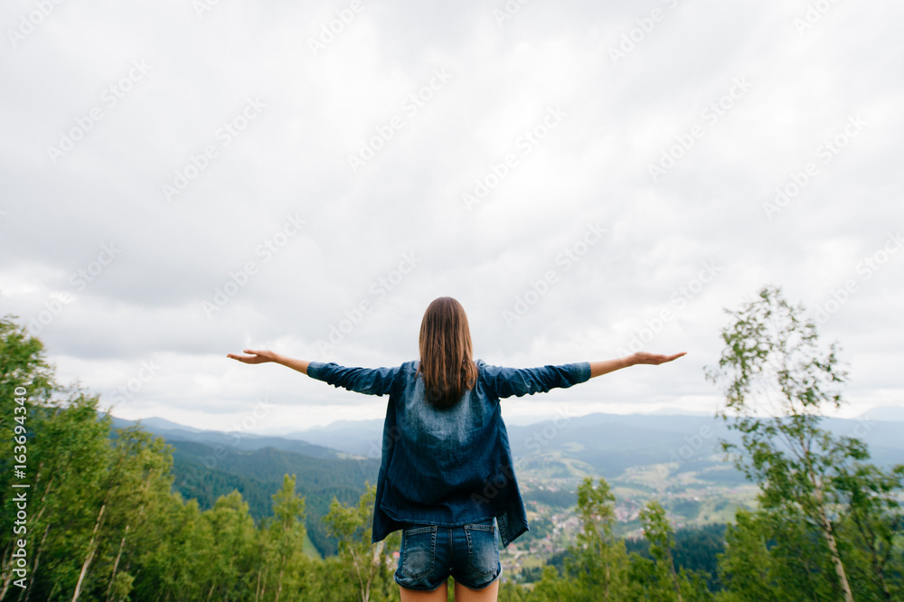 Fototapeta Woman in wild nature asking sky for blessing and enjoying  nature greatness. Relaxation, meditation, harmony of inner life and mind. Unity of human and world. Exaltation of heart and consciousness.