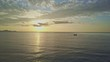 Drone Moves to Boat Sailing across Ocean against Sun Reflection