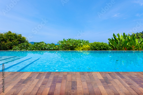 Deurstickers Tropical strand Swimming pool overlooking view andaman sea mountains and blue sky background,summer holiday background concept.