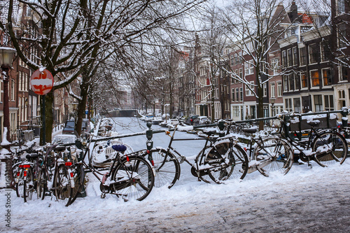 Iced up bicycles and canal boats around a frozen canal in Amsterdam overlooked by deciduous trees and brick terrace houses. #163718159